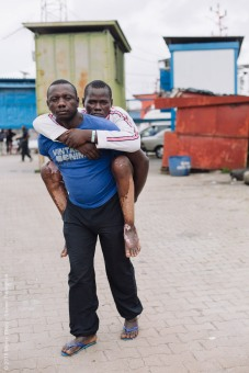 Ibrahima, plastics patient, being carried by his brother before surgery.