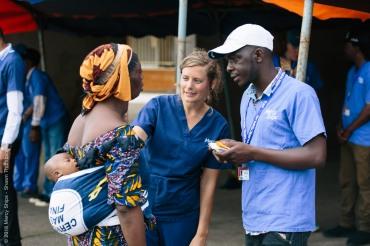 Mirjam Hamer, Screening Nurse, talking to a potential patient at the mass screening at Palais du Peuple.