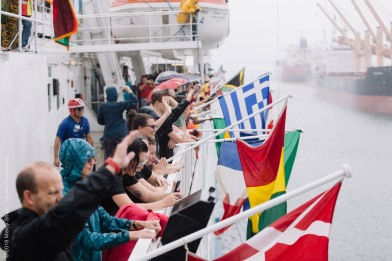 Crew members wave their flags as the Africa Mercy arrives into the Port of Conakry.