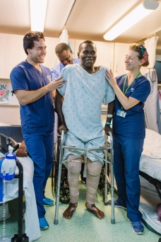 Ibrahima, plastics patient, walking for the first time in the ward after surgery with the help of Allan Kent and Laura Blundell, Physical Therapists.